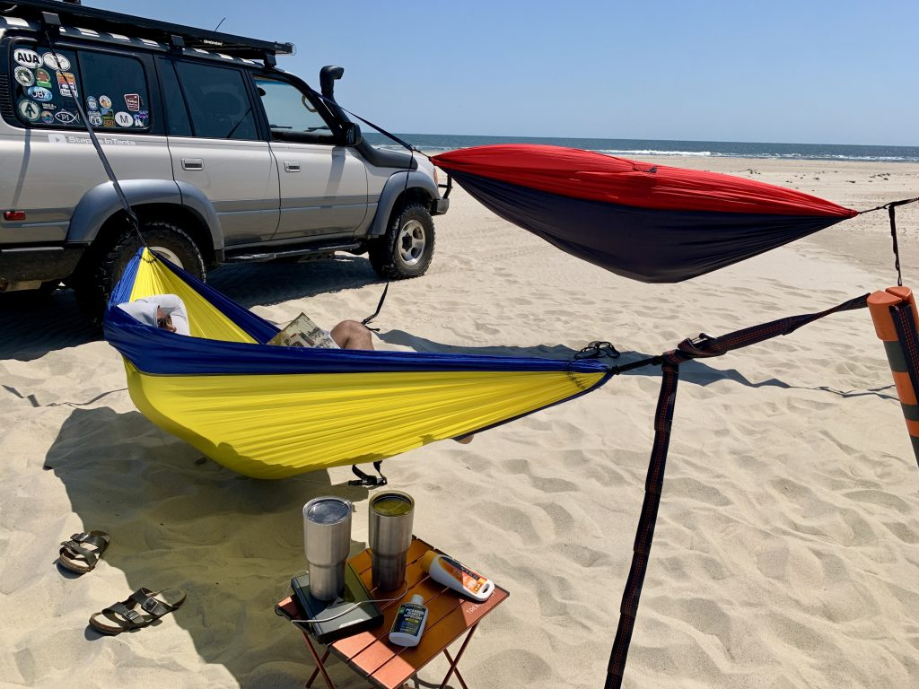 Laying a hammock on the beach using trucks