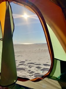 Sunrise beach view from inside of a tent.
